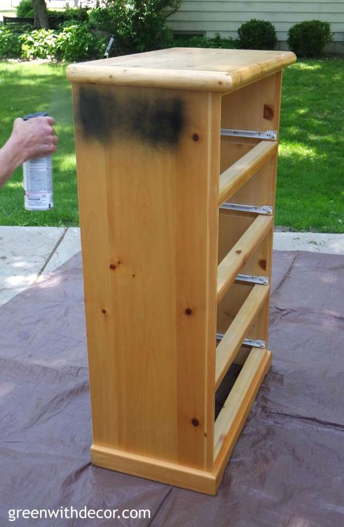 Painting a dresser with black spray paint, a dresser sitting on a brown tarp