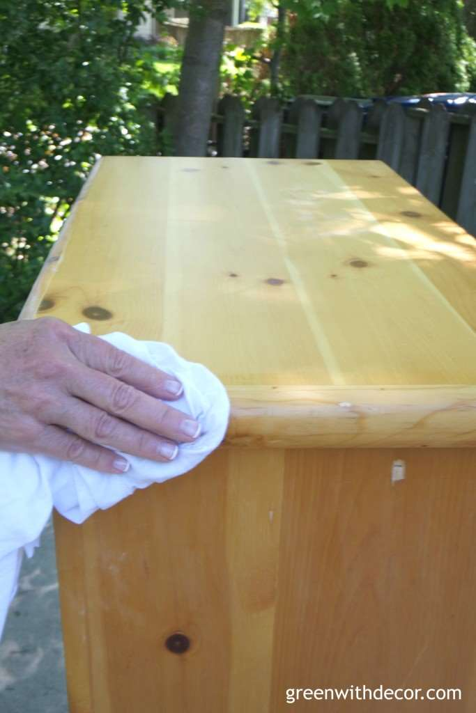 A wood dresser being wiped down before being spray painted