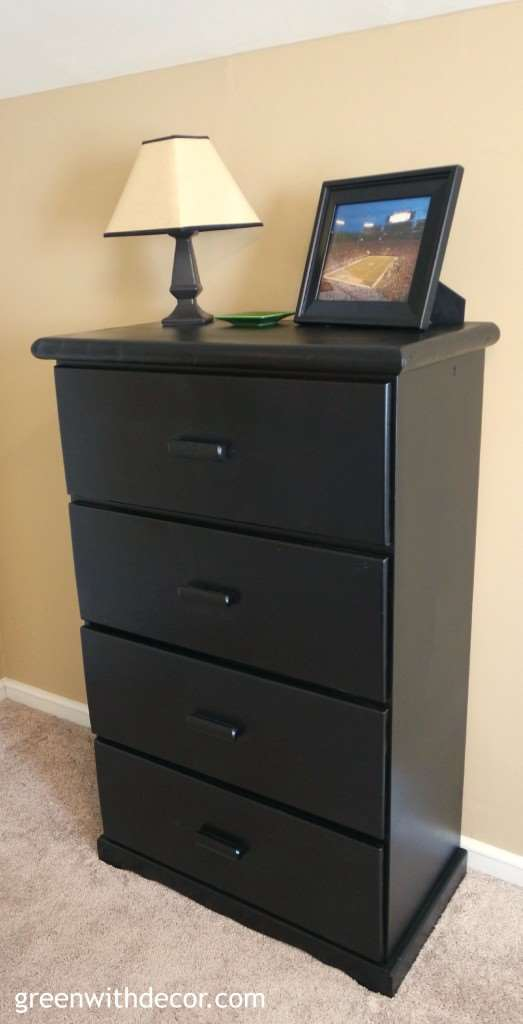 A black painted dresser near a tan wall and tan carpet