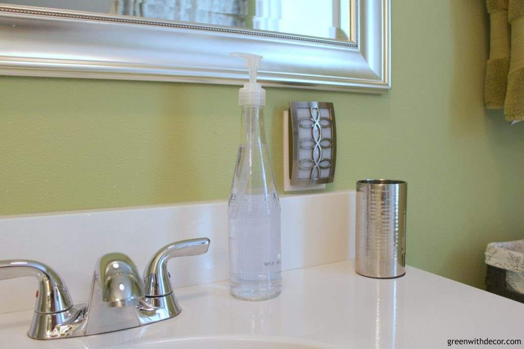 A DIY beer bottle soap dispenser on a white counter
