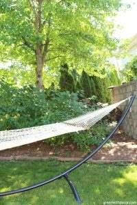 Relaxing with a hammock in the backyard. Love the sleek look of that black hammock stand!