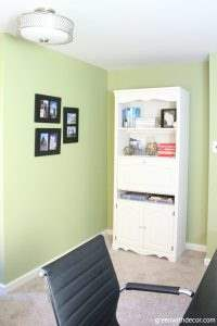 White painted bookshelf with crystal knobs. Walls are Ryegrass green.