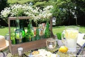How to easily decorate a rental patio plus a great idea for a summer centerpiece using an old wood toolbox and glass bottles. Love how she updated this old patio for summer!