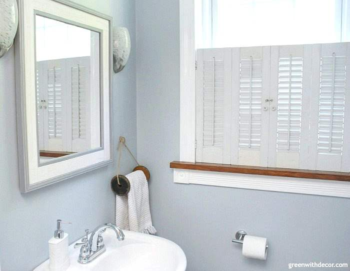 Small bathroom makeover for just $100. Perfect for renters! Love the coastal and farmhouse design - the towel rack is an old wooden spool. Great storage for a small bathroom!