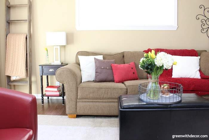 Camelback walls in a tan and red family room. Dark couch with brown, white and red throw pillows. Ladder blanket shelf.