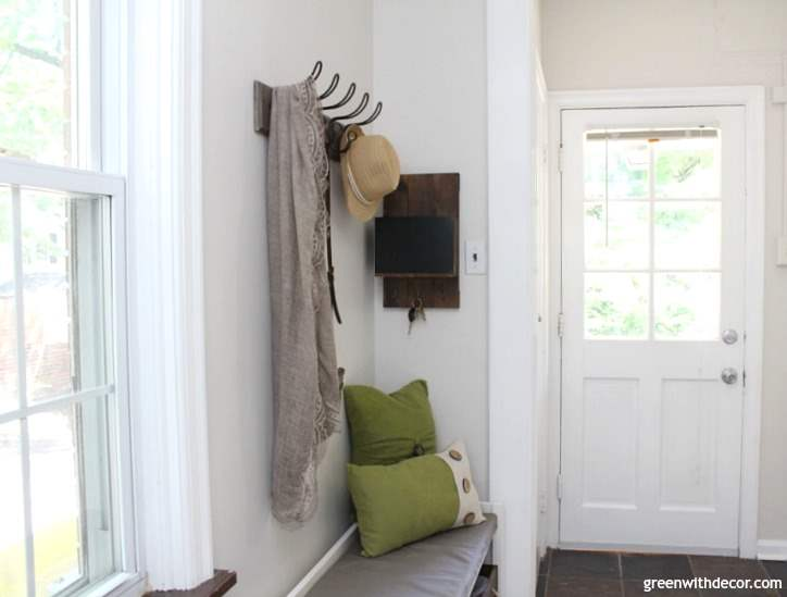 How to design a small back foyer, 4 great elements to think about when designing any room in the house. Love how she turned this blank wall into a mudroom/back entryway. Great storage ideas for shoes, coats, purses, the dog leash and keys. Fun rustic, coastal look. Pretty white paint color on the walls, too.