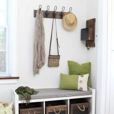 Mudroom with Aesthetic White walls, a white bench, green pillows and wood hooks