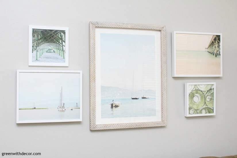 Tips to plan a gallery wall, including narrowing down artwork choices, how to pick pieces for a cohesive look and how many pieces do use. Love the beachy artwork in this living room! Paint color is Agreeable Gray.