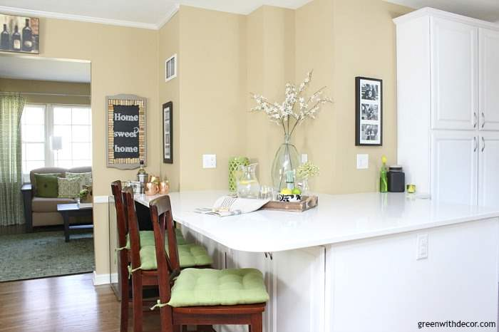 Such a pretty tan paint color! It's Sherwin Williams' Camelback, such a nice warm neutral! Looks great in this white kitchen with green and aqua accents!