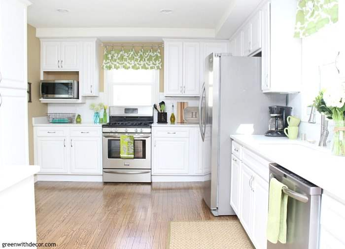 Beautiful white kitchen renovation. Pretty white quartz counters, white cabinets and stainless steel appliances. Beautiful neutral kitchen with pops of green and aqua - fun for a coastal or beachy look! Love the white subway tile.
