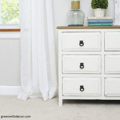 A short white dresser with a wood top and black hardware. Agreeable Gray walls with white curtains, white trim and tan carpet.