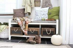 A white bench with wood crates for shoe storage and throw pillows on top of the bench.