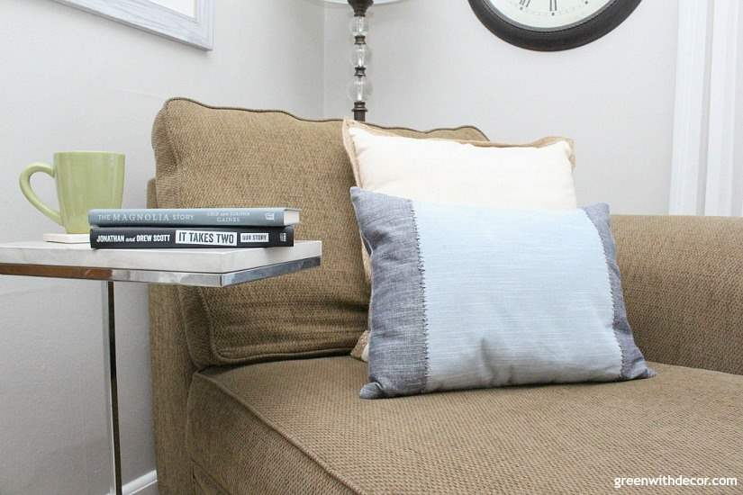 A dark brown chaise with blue and white pillows, a white and silver side table with books by HGTV stars.