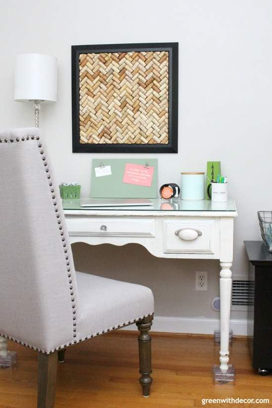 A gray home office with a DIY cork bulletin board and painted desk