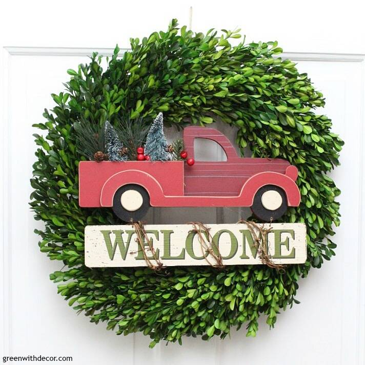 Christmas decorating ideas for the foyer. Gorgeous Christmas boxwood wreath with the red truck and Christmas tree on the white door!