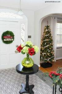 Christmas decorating ideas for the foyer. What a gorgeous view with the Christmas tree, boxwood wreath, red pickup truck with Christmas tree and those flowers!