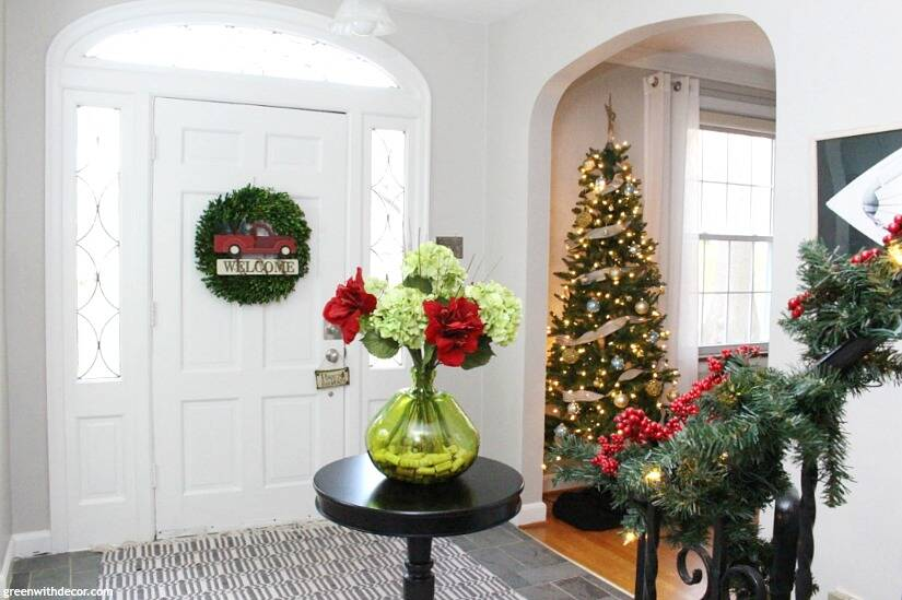 a big foyer decorated for christmas with agreeable gray walls a white wood door with - Christmas Decorating Ideas For Foyer