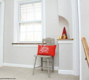 Christmas decorating ideas for a hallway. Love that mini red Christmas tree and the clay painted chair! Wall color is Agreeable Gray.