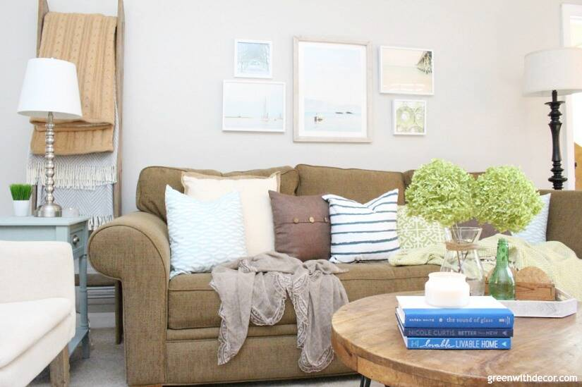 The costal rustic living room reveal - gorgeous beachy coastal living room with budget-friendly decorating and DIY projects. Love that coastal gallery wall and all the furniture makeovers. Love that modern round wood coffee table and all of the coastal throw pillows.
