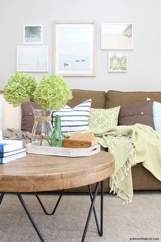 The costal rustic living room reveal - gorgeous beachy coastal living room with budget-friendly decorating and DIY projects. Love that coastal gallery wall and all the furniture makeovers. I want that! modern round wood coffee table!