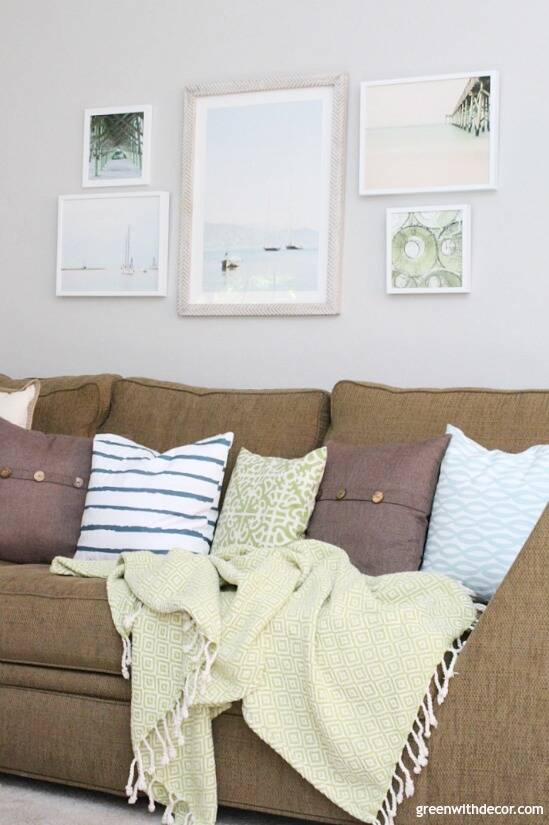 The costal rustic living room reveal - gorgeous beachy coastal living room with budget-friendly decorating and DIY projects. The dried hydrangeas are so pretty. Love those blue, white and green coastal throw pillows - they brighten up that dark couch!