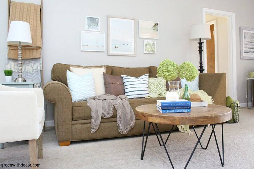 The costal rustic living room reveal - gorgeous beachy coastal living room with budget-friendly decorating and DIY projects. That coastal gallery wall looks great, and the green dried hydrangeas are so pretty. Love those blue, white and green coastal throw pillows - they brighten up that brown couch!