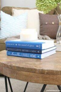 Rustic round wood coffee table with blue interior design coffee table books with a candle and throw pillows in the background.