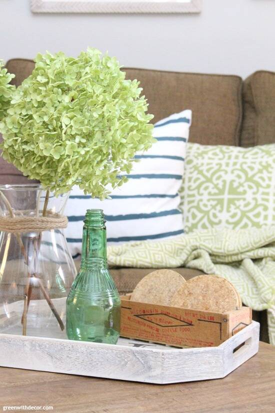 The costal rustic living room reveal - gorgeous beachy coastal living room with budget-friendly decorating and DIY projects. These green dried hydrangeas are so pretty. Love those blue, white and green coastal throw pillows - they brighten up that dark couch!