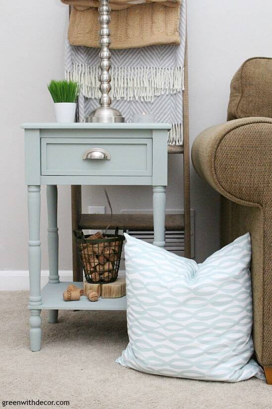 A blue painted end table with a blue and white pillow