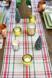 A pretty plaid Christmas centerpiece and tablescape with candles, a plaid table runner, berries and old wine bottles. Love how simple the pieces are in this centerpiece and how it all comes together in such a pretty way for a holiday table!