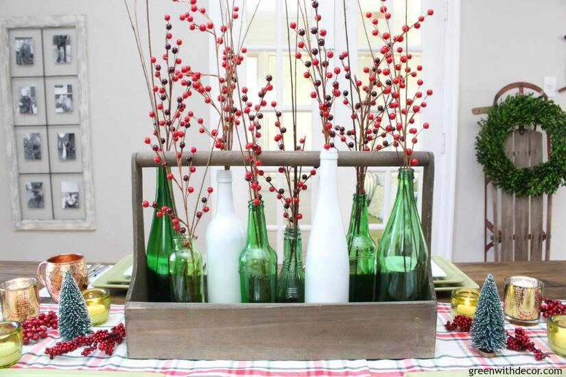 A plaid Christmas centerpiece and tablescape. Love the pretty old bottles with the red Christmas berries and ornaments.