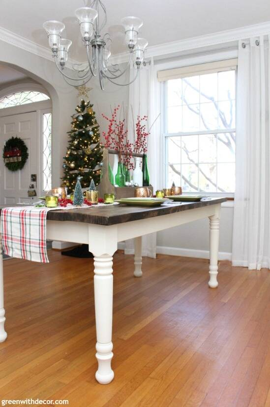 A plaid Christmas centerpiece and tablescape. Love those pretty bottles with the Christmas berries and ornaments. And that gorgeous farmhouse dining table - they built it!