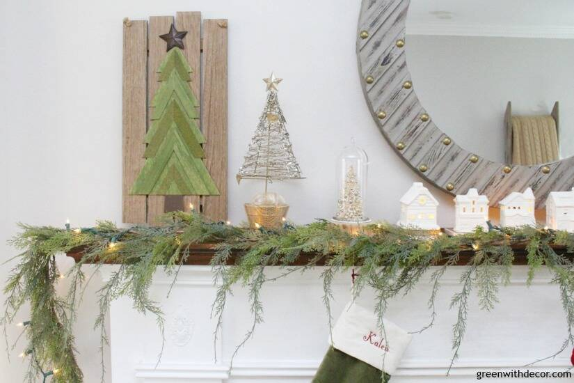 A simple Christmas mantel with village pieces, that faux garland looks real - I love it!