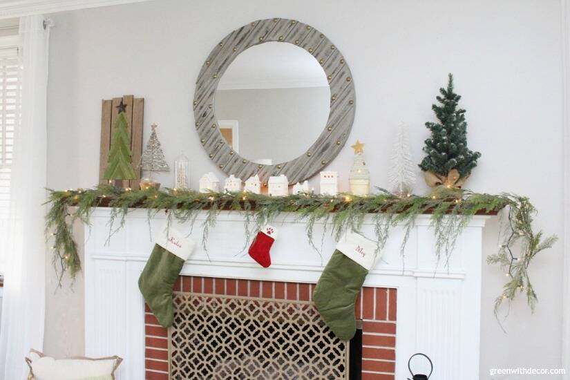 A simple Christmas mantel with village pieces, pretty faux garland and white lights