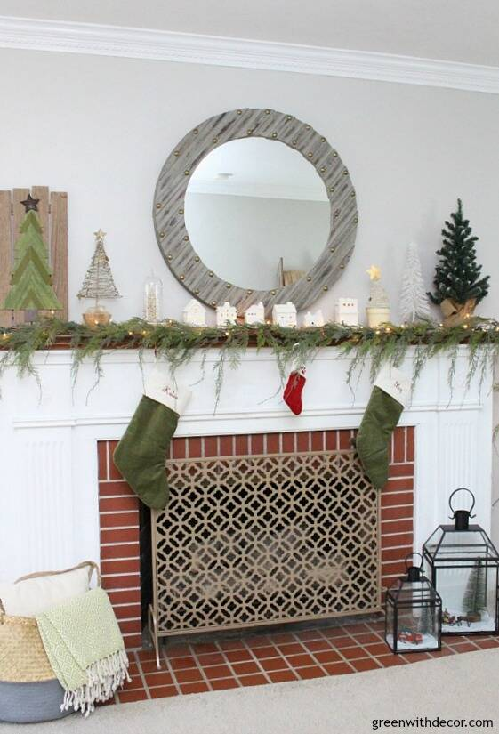 A simple Christmas mantel with village pieces, that faux garland looks real - I love it with the white Christmas lights and all the mini Christmas trees, so easy and festive!