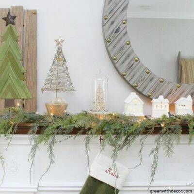 A simple Christmas mantel with village pieces and pretty faux garland