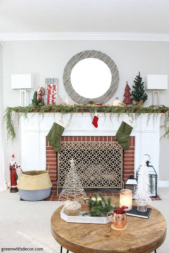 A traditional Christmas living room filled with red, green and metallic decor. Love that faux garland and all of the Christmas pillows! Plus those little lantern Christmas villages are too cute!