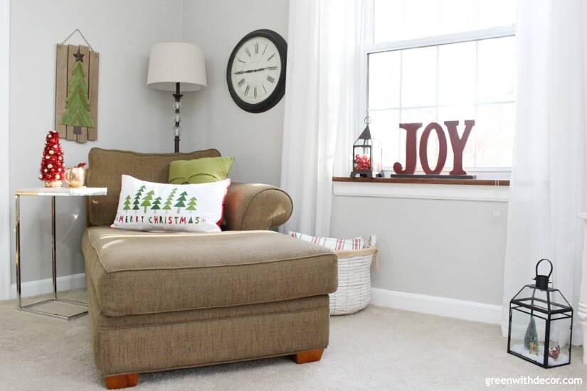 A traditional Christmas living room filled with red, green and metallic decor. Cute wood JOY sign in the window, good use of space!