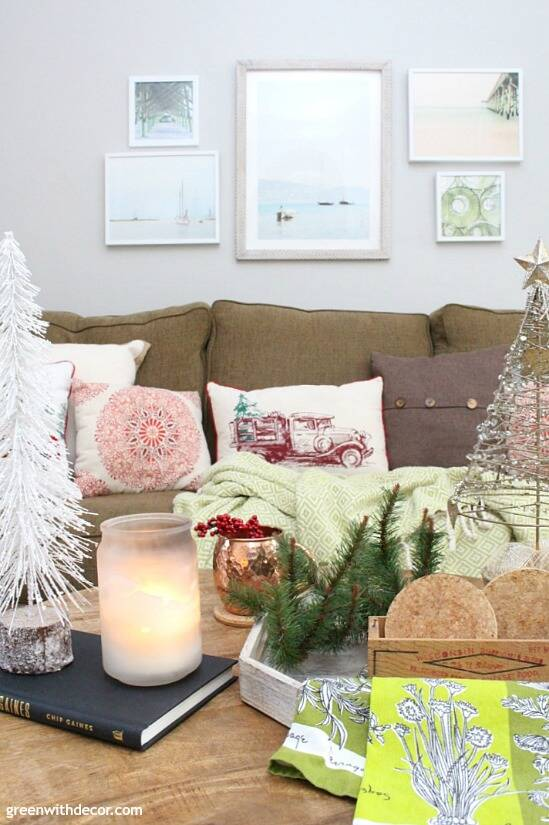 A traditional Christmas living room filled with red, green and metallic decor. Love all of the mini Christmas trees and festive pillows!