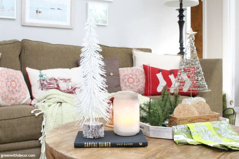A traditional Christmas living room filled with red, green and metallic decor. Gorgeous white mini Christmas tree, love the wood base!