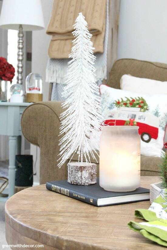 A traditional Christmas living room filled with red, green and metallic decor. Such a gorgeous white mini Christmas tree, love the wood base!