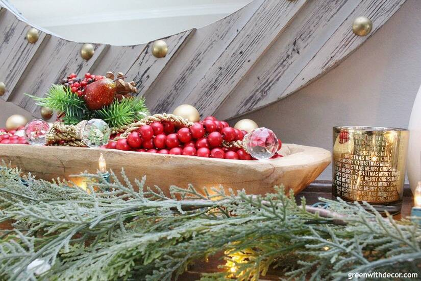 A traditional Christmas mantel - full of red, green, metallic and neutral pieces. Love that faux garland, metallic candles and bread bowl!