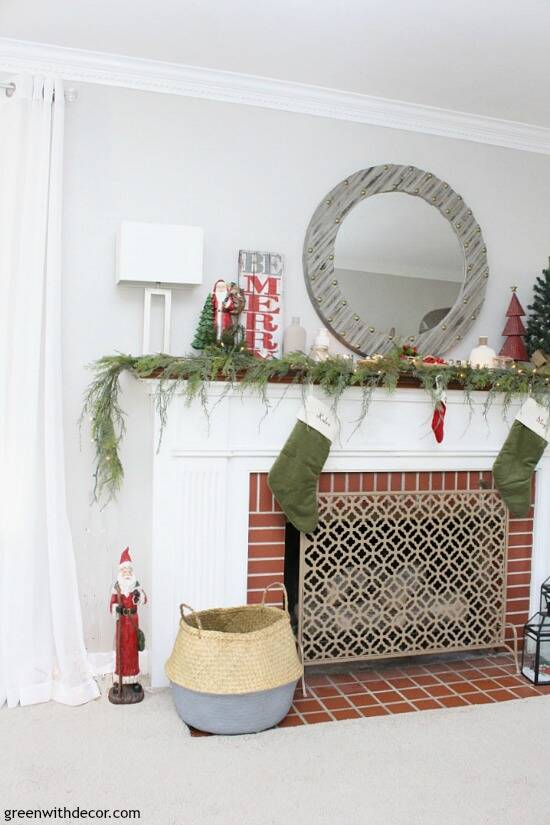 A traditional Christmas mantel - full of red, green, metallic and neutral pieces. Love that faux garland and gorgeous gray wood mirror!