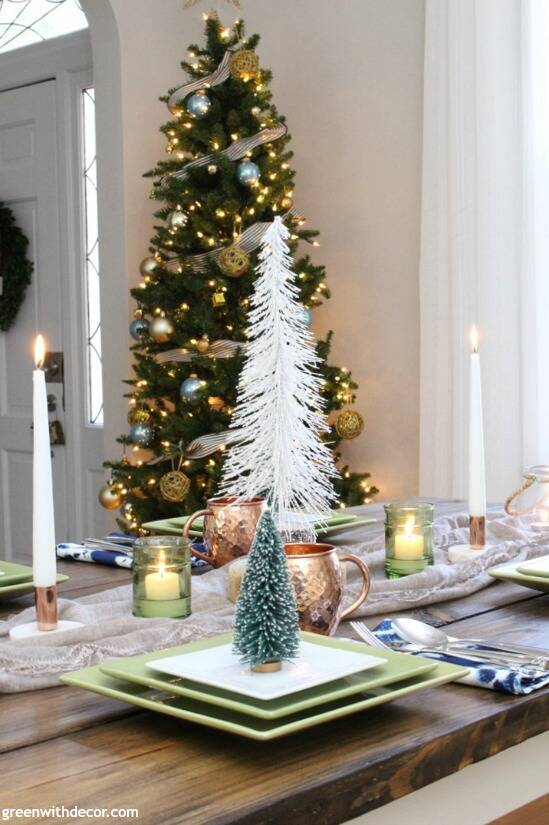 A blue and copper Christmas centerpiece + tablescape - perfect for a costal tablescape! Love the tree in the corner of the dining room and all of those pretty mini Christmas trees for the centerpiece on the table!
