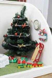 A miniature Christmas living room. That little wreath and sled are SO cute for a dollhouse at Christmas!