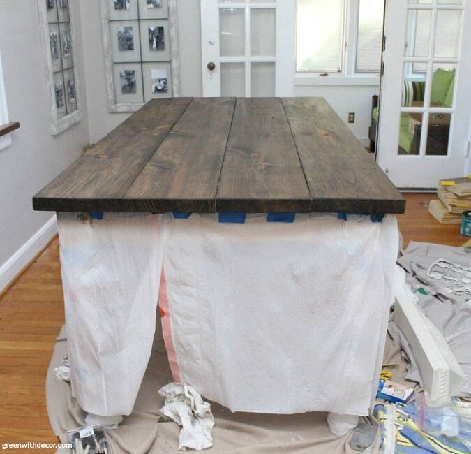 A dark stained wood farmhouse table in the process of being stained, with garbage bags around it to protect the table legs.