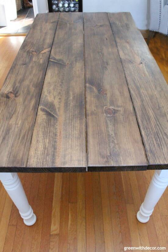 A dark stained wood farmhouse table with white spindle legs, sitting on a hardwood floor.