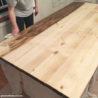 An unfinished wood farmhouse table in the process of being stained with dark wood stain.