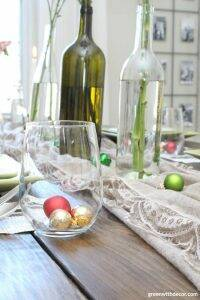 A simple Christmas centerpiece + tablescape with wine bottles, flowers, candles and ornaments. So cute to use ornaments as wine glass filler until dinner!