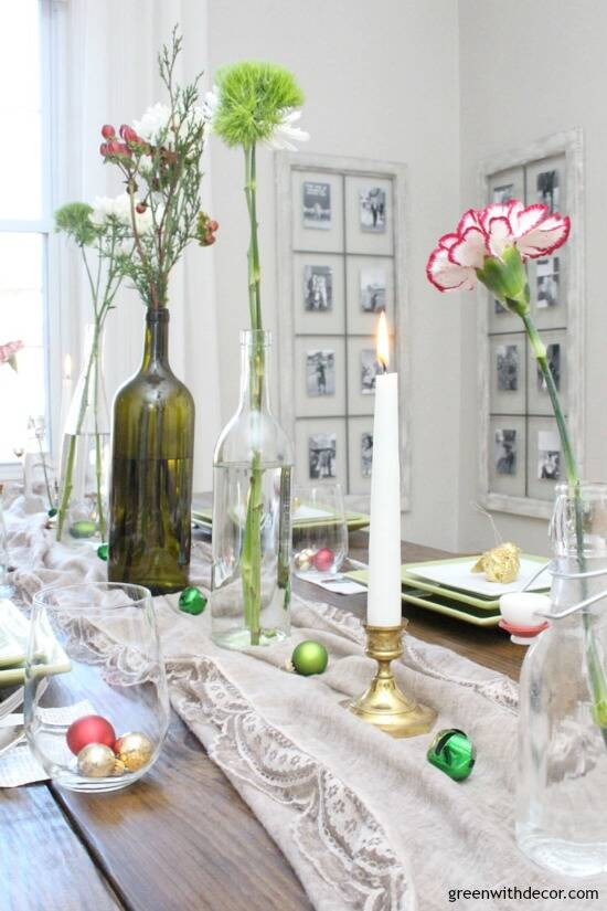A simple Christmas centerpiece + tablescape with wine bottles, grocery store flowers, candles and little ornaments and jingle bells. This is so easy to put together for a Christmas or New Years party!